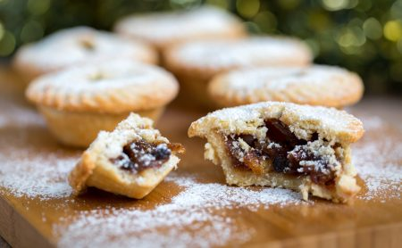 Mince pies photographed with filling exposed and dusted with icing sugar.