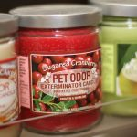 Pet Odor Exterminator candle close-up in retail display.